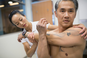 Physical therapist guiding patient stretching armの写真素材 [FYI02277515]