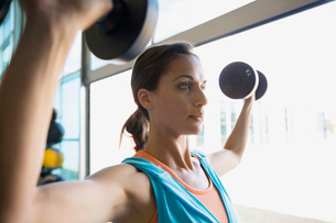 Close up focused woman doing dumbbell shoulder pressesの写真素材 [FYI02277584]
