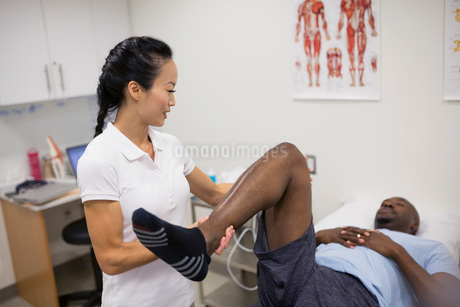 Physical therapist stretching patient leg in examination roomの写真素材 [FYI02277603]