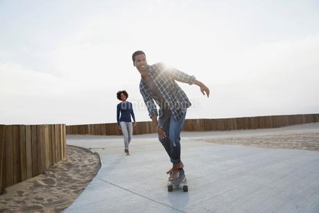 Man skateboarding on beach pathの写真素材 [FYI02277617]