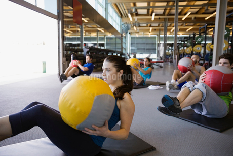 Exercise class doing seated medicine ball twists gymの写真素材 [FYI02277620]