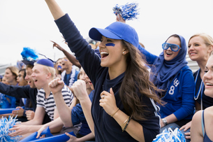 Cheering woman in blue in bleachers sports eventの写真素材 [FYI02277653]