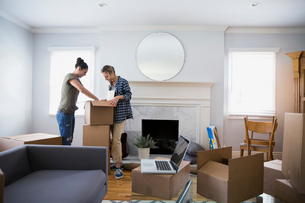 Lesbian couple unpacking moving boxes in living roomの写真素材 [FYI02277655]