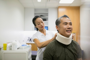 Physical therapist placing neck brace on patientの写真素材 [FYI02277659]