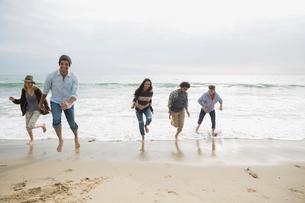 Friends running from ocean surf onto beachの写真素材 [FYI02277670]