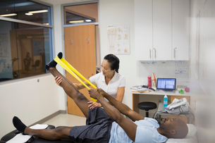 Physical therapist guiding patient using resistance band legの写真素材 [FYI02277679]