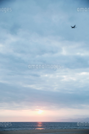 Plane in overcast sunset sky over oceanの写真素材 [FYI02277696]
