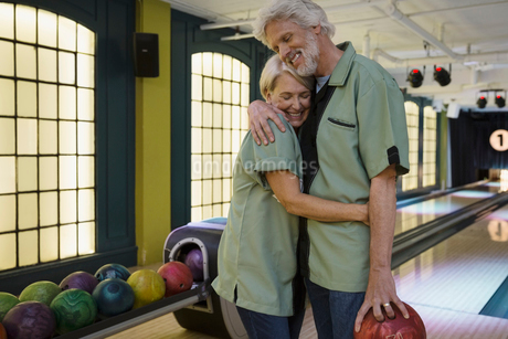 Couple in bowling shirts hugging at bowling alleyの写真素材 [FYI02277737]