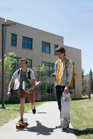 College students skateboarding on sunny campus sidewalkの写真素材 [FYI02277756]