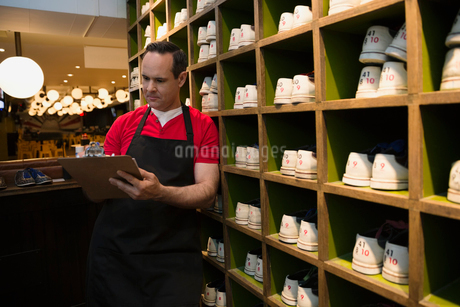 Worker with clipboard next to bowling shoesの写真素材 [FYI02277814]