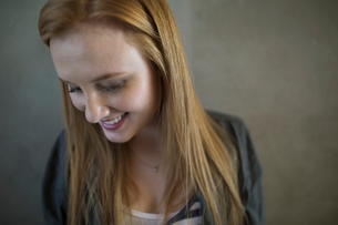Portrait smiling young woman red hair looking downの写真素材 [FYI02277958]
