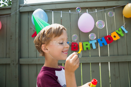 Boy wearing birthday party hat blowing bubblesの写真素材 [FYI02277966]