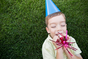 Boy in party hat blowing party horn blowerの写真素材 [FYI02277983]