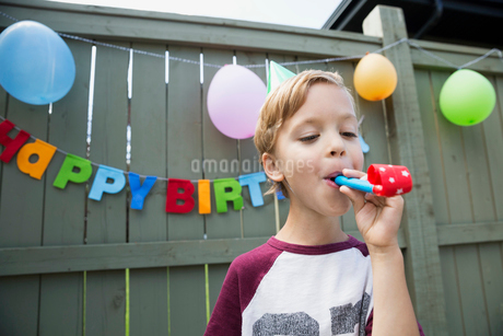 Boy blowing party favor wearing birthday party hatの写真素材 [FYI02278028]
