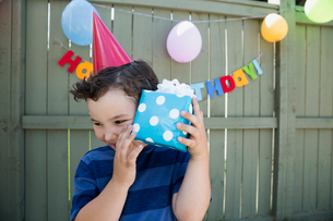 Boy wearing birthday party hat shaking wrapped giftの写真素材 [FYI02278031]