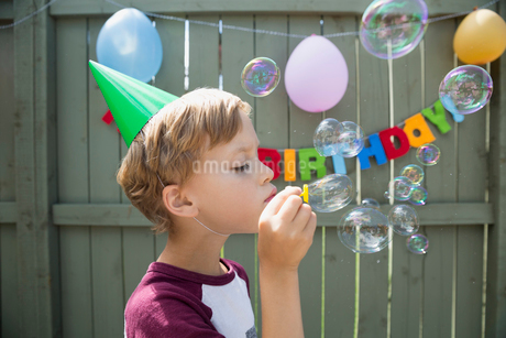 Boy wearing birthday party hat blowing bubblesの写真素材 [FYI02278040]