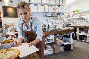 Tea shop owner doing paperwork at counterの写真素材 [FYI02278042]