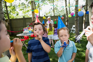 Kids in birthday party hats blowing party favorsの写真素材 [FYI02278050]