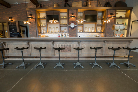 Stools lined along empty distillery barの写真素材 [FYI02278069]