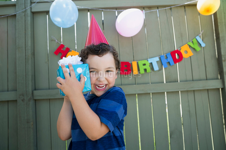 Enthusiastic boy wearing birthday party hat holding giftの写真素材 [FYI02278154]