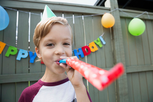 Portrait boy blowing party favor birthday party hatの写真素材 [FYI02278175]