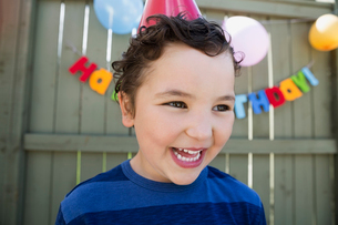Close up enthusiastic boy wearing birthday party hatの写真素材 [FYI02278221]