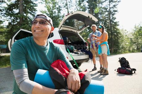 Smiling backpacker near carの写真素材 [FYI02278308]
