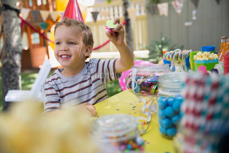 Boy wearing birthday party hat holding candyの写真素材 [FYI02278312]