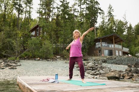 Mature woman practicing warrior 2 yoga pose dockの写真素材 [FYI02278526]