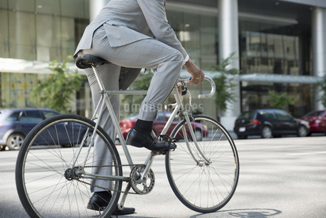 Businessman in suit riding bicycle on city streetの写真素材 [FYI02278624]