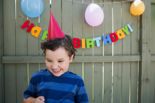 Enthusiastic boy wearing birthday party hatの写真素材 [FYI02278738]