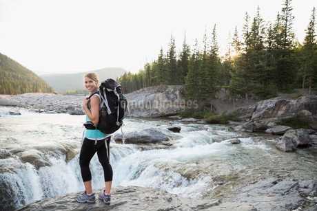 Portrait smiling hiker with backpack at craggy waterfallの写真素材 [FYI02278748]