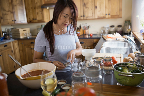 Woman canning tomato sauce in kitchenの写真素材 [FYI02278789]