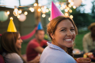 Portrait smiling woman party hat backyard birthday partyの写真素材 [FYI02278840]