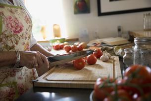 Woman cutting tomatoes on cutting boardの写真素材 [FYI02279005]