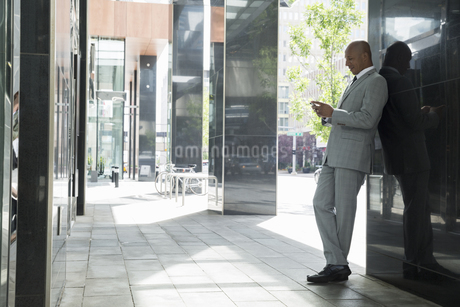 Businessman texting with cell phone on urban sidewalkの写真素材 [FYI02279085]