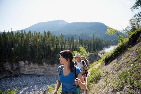 Hikers walking along craggy ridge above riverの写真素材 [FYI02279220]