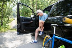 Senior man with mountain bike tying shoelace carの写真素材 [FYI02279275]