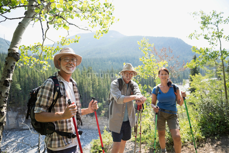 Portrait confident hikers with poles on trailの写真素材 [FYI02279454]