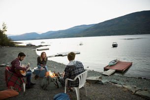 Young friends relaxing around lakeside campfireの写真素材 [FYI02279538]