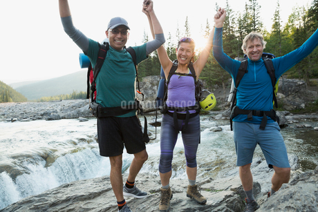 Portrait enthusiastic hikers with arms raised in riverの写真素材 [FYI02279739]