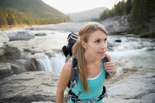Female hiker with backpack hiking on craggy riversideの写真素材 [FYI02279741]