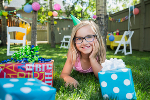 Portrait smiling girl birthday party hat gifts grassの写真素材 [FYI02279779]