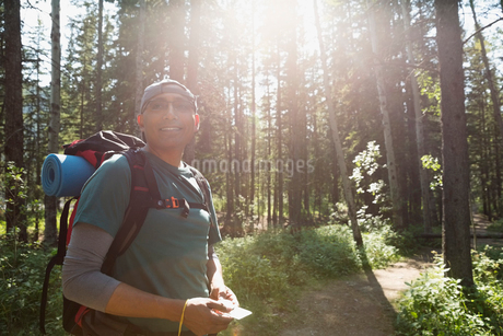 Smiling backpacker with compass in sunny woodsの写真素材 [FYI02279782]