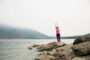 Mature woman practicing yoga on rock at lakesideの写真素材 [FYI02279790]