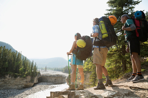 Hikers with backpacks looking at river viewの写真素材 [FYI02279897]