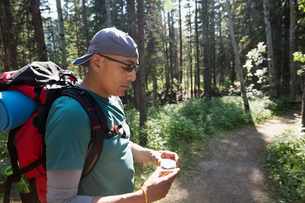 Backpacker checking compass on trail in woodsの写真素材 [FYI02279939]