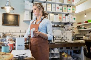 Smiling tea shop owner preparing tea behind counterの写真素材 [FYI02279952]