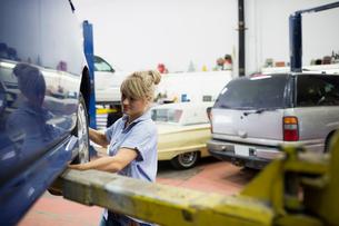 Female mechanic replacing tire on carの写真素材 [FYI02280034]