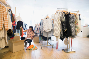 Business owner unpacking new inventory in clothing shopの写真素材 [FYI02280081]